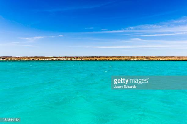 Clear turquoise tropical seas against an Outback desert coastline.