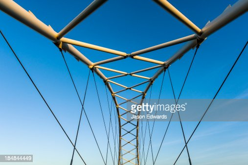 Steel girders of a residential foot bridge arching over a tidal canal.