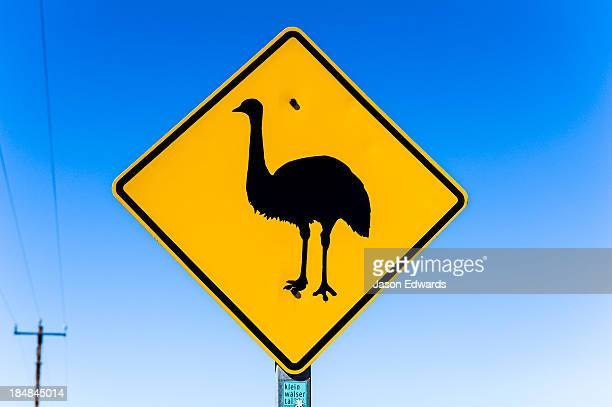 An Emu wildlife warning sign near a remote town in the desert.