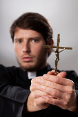 Exorcist holding a crucifix and making his prayers