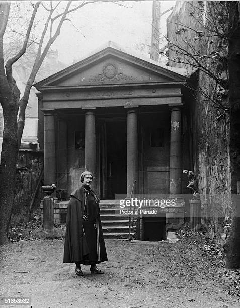 Expatriate American author and salon hostess Natalie Clifford Barney wears a cape and stands in front of a Greekstyle temple in the garden of her...