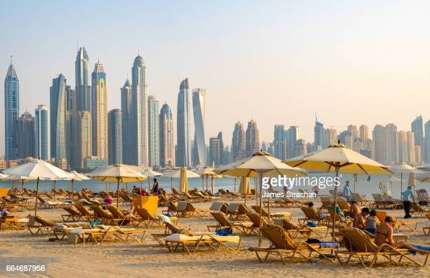 Expatriates sunning themselves on loungers with umbrellas in the evening sun on Fairmont Hotel beach on the Palm, Jumeirah opposite the looming skyscrapers of Dubai