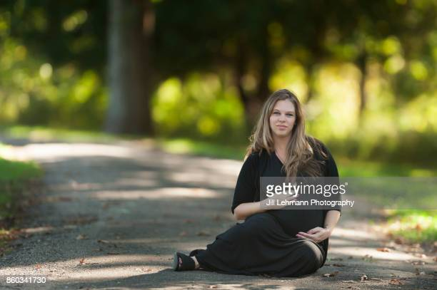 Expectant Blonde Twin Mother in Maternity Dress Sits in Park