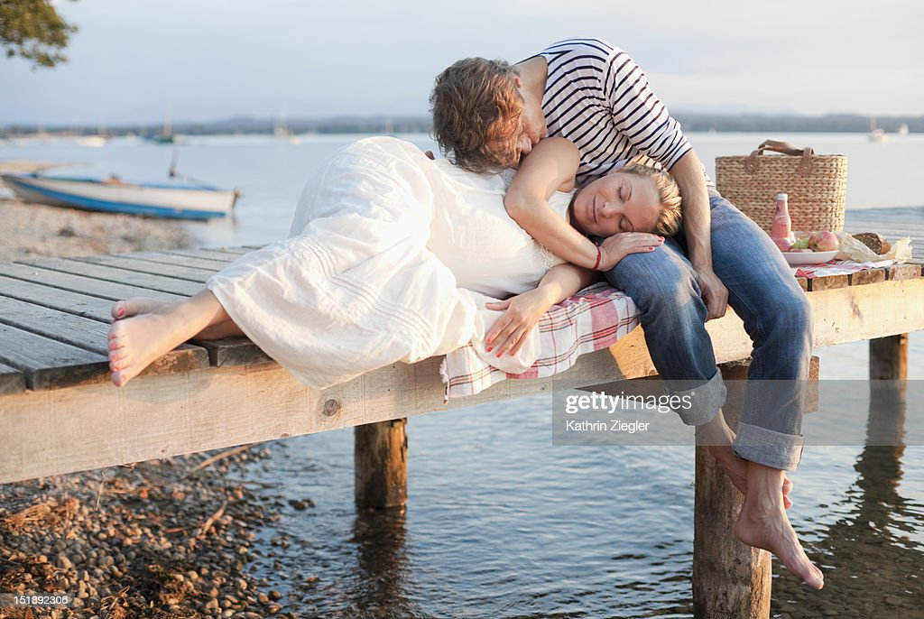 expectant couple relaxing on the jetty at sunset : Stock Photo