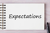 Top view of Expectations text on notebook with a marker.