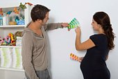 Expecting couple with paint swatches in nursery