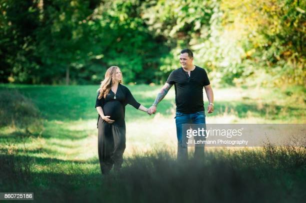 Expecting Mother of Twins walks with Husband in field
