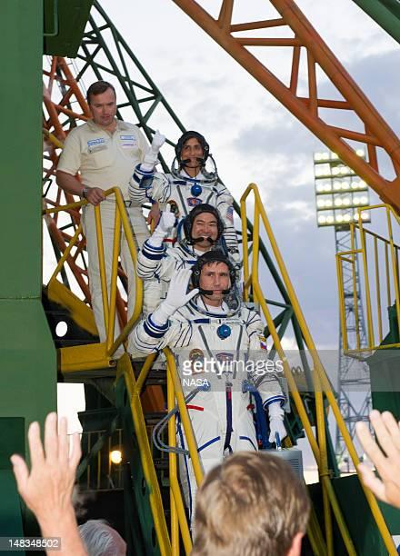 Expedition 32 Soyuz Commander Yuri Malenchenko bottom JAXA Flight Engineer Akihiko and NASA Flight Engineer Sunita Williams top wave farewell from...