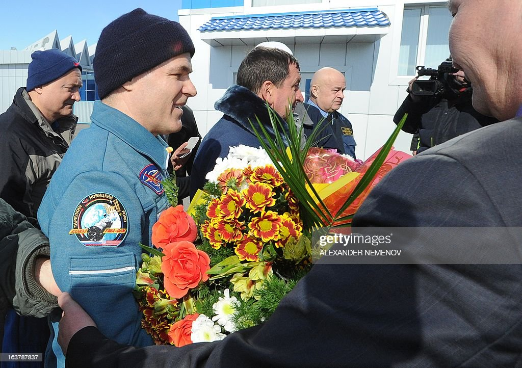 Expedition 34 Commander Kevin Ford of NASA (L) receives flowers at the airport of Kostanay, on March 16, 2013, after the landing in northern Kazakhstan. The three astronauts, Kevin Ford, Russian Soyuz Commander Oleg Novitskiy and Russian Flight Engineer Evgeny Tarelkin, returned safely to Earth from the International Space Station early today, aboard a Russian capsule which landed on the freezing Kazakhstan steppe, mission control said. AFP PHOTO / POOL / ALEXANDER NEMENOV
