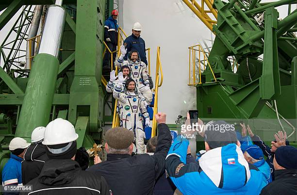Expedition 49 flight engineer Andrey Borisenko of Roscosmos Shane Kimbrough of NASA and Soyuz commander Sergey Ryzhikov of Roscosmos wave farewell...