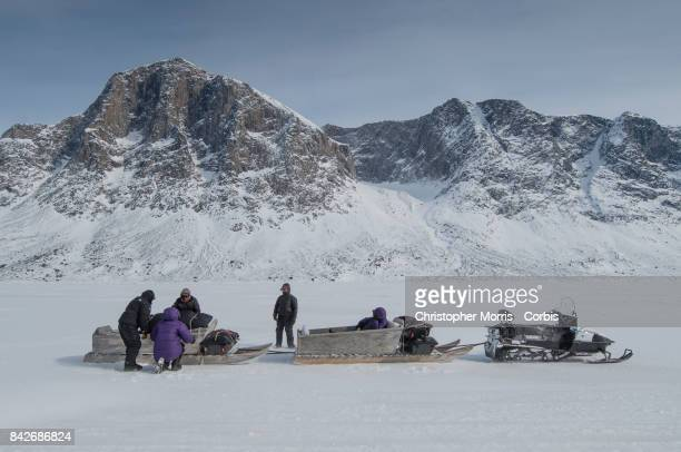 Expedition members load gear on to a snowmobile and qamutik to cross the sea ice of Pangnirtung Fiord in Auyuittuq National Park on April 16 2017 on...