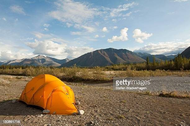 Expedition tent on a gravel bar, Northern Mackenzie Mountains behind, camping, Wind River, Yukon Territory, Canada