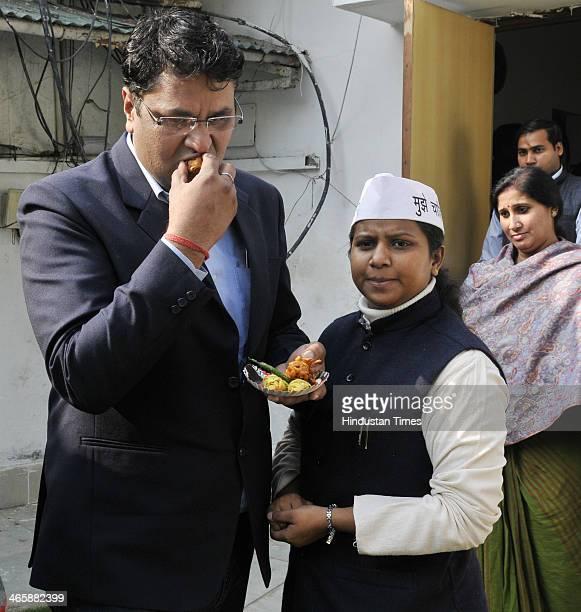 Expelled Aam Aadmi Party MLA Vinod Kumar Binny eating snacks while AAP leader and Delhi Minister for Women and Child Development Rakhi Birla looks on...