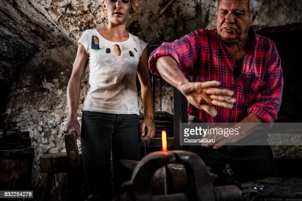 Experienced Senior Blacksmith Man Explaining to Young Practitioner Woman How to Do it