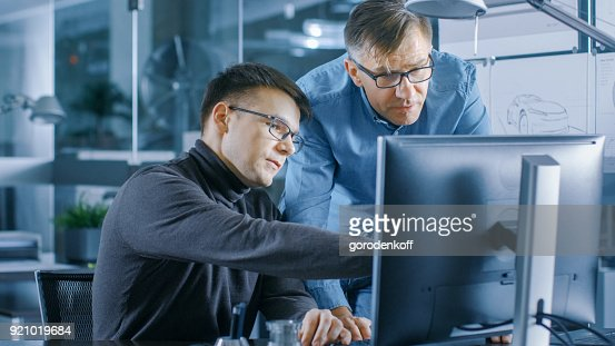 Experienced Senior Engineer Consults Young Designer about Project, They Have Discussion and Work on a Personal Computer. : Stock Photo