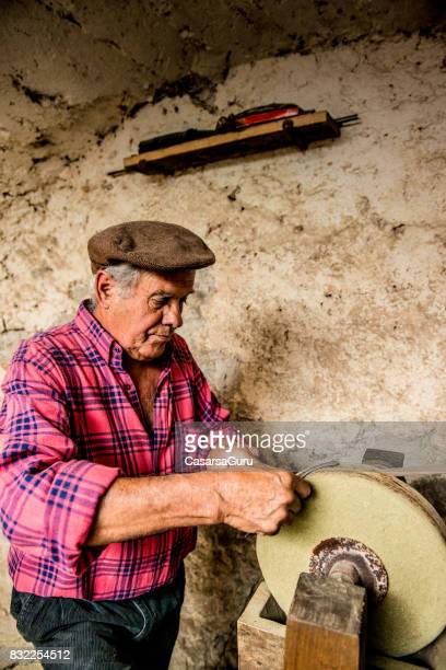 Experienced Senior Man Sharpen a Sickle on Grinding Stone