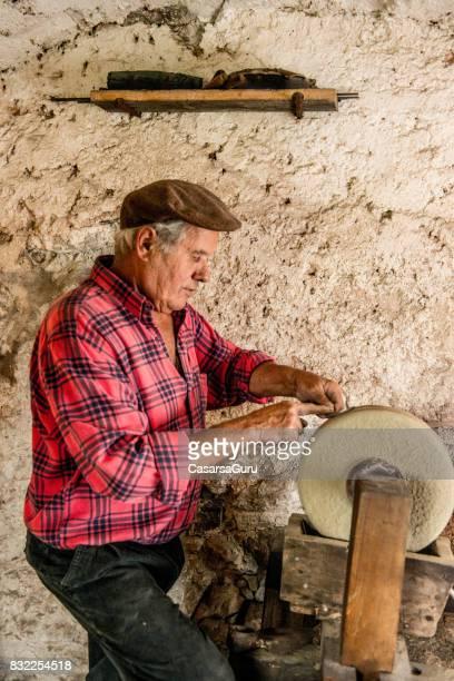 Experienced Senior Man Sharpen Sickle on Grinding Stone