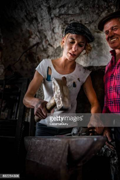 Experienced Senior Man Teaching Young Practicant Woman to Forging
