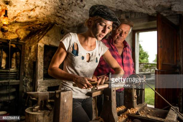 Experienced Senior Man Teaching Young Woman how to use the Lathe