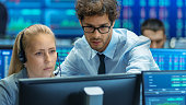 Experienced Stock Exchange Trader Teaches His Apprentice at Her Workstation. Multi-Ethnic Team at Stock Exchange Office is Busy Selling and Buying Stocks on the Market. Displays Show Relevant Data Num