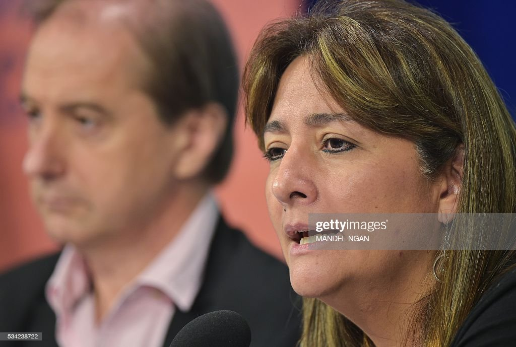 Expert Carlos Martín Beristain (L) of Spain watches as fellow expert Angela Buitrago of Colombia speaks on the report by the Interdisciplinary Group of Independent Experts on the disappearance of 43 students from the Rural Teachers College in Ayotzinapa, Mexico at the Wilson Center's Mexico Institute on May 25, 2016 in Washington, DC. / AFP / MANDEL