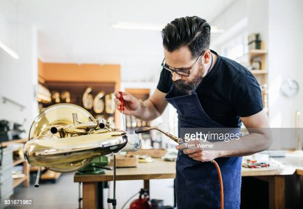 Expert Craftsman Applying Repairs To Damaged Musical Instrument