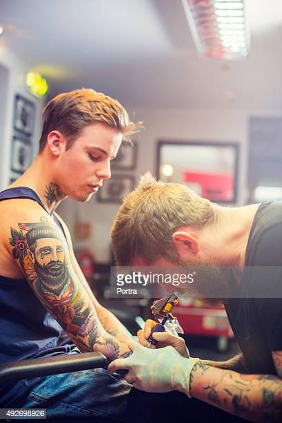 Expert making tattoo on man's hand