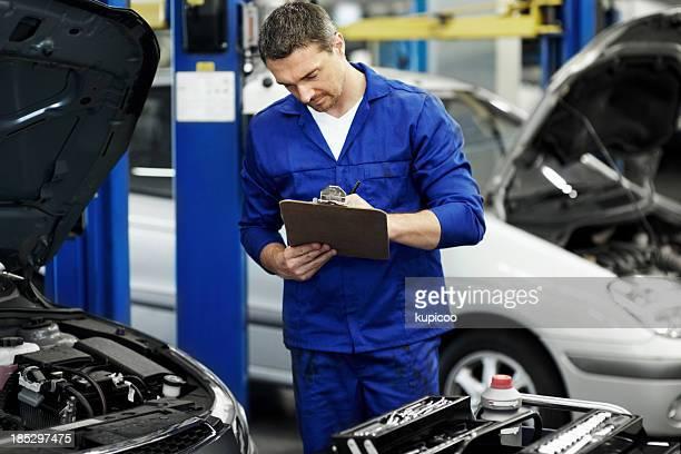 Expert mechanic taking notes