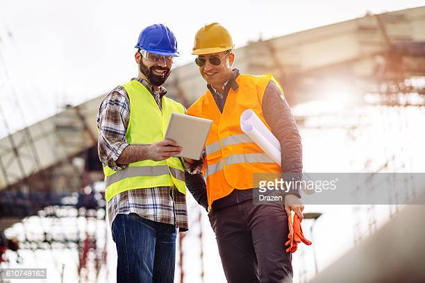 Experts having meeting on construction site and using digital tablet