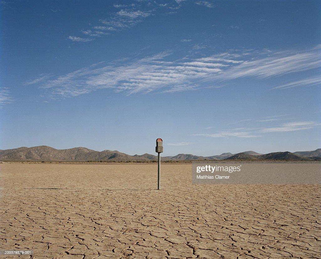 Expired parking meter in desert : Stock Photo