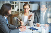 Young businesswoman explaining something to colleague at meeting