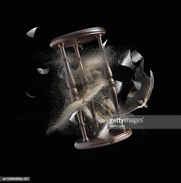 Exploding hourglass on black background, digital composite