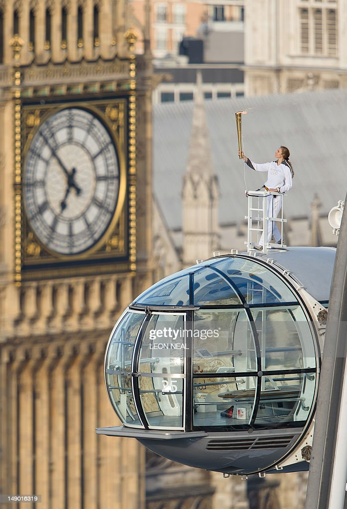 Explorer Amelia Hempleman-Adams holds the Olympic torch as she stands on top of one of the pods on the London Eye in central London on July 22, 2012. The London 2012 Olympic Games begin on July 27. AFP PHOTO / LEON NEAL