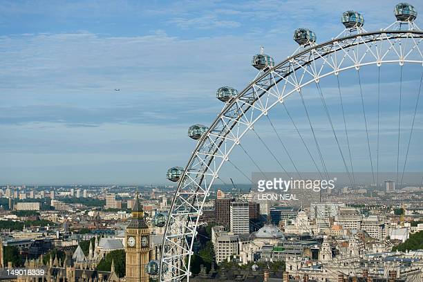 Explorer Amelia HemplemanAdams holds the Olympic torch as she stands on top of one of the pods on the London Eye in central London on July 22 2012...