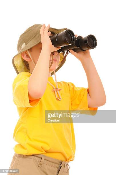 Explorer, curious young boy looking up through binoculars