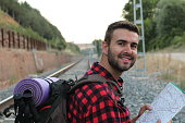 A portrait of a man with backpack arriving at the train station isolated about to start El Camino de Santiago in Spain or France.