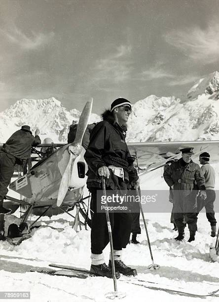 circa 1950 New Zealand mountaineer Sir Edmund Hillary stands near an Auster plane as he prepares to move off on skis