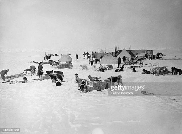 Explorers sled dogs and supplies cover the ice around the hut and tents of the base camp on the Ross Ice Shelf during Shacklton's British Antarctic...