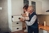 Elderly man looking inside a drawer with his granddaughter