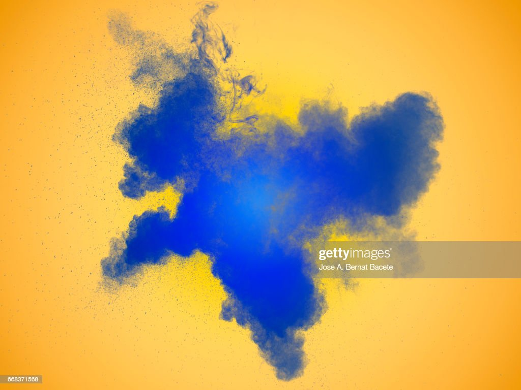 Explosion of a cloud of powder of particles of  color blue on a orange background : Stock Photo