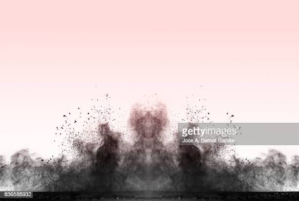 Explosion of a cloud of powder of particles of colors gray and black and a pink vintage background