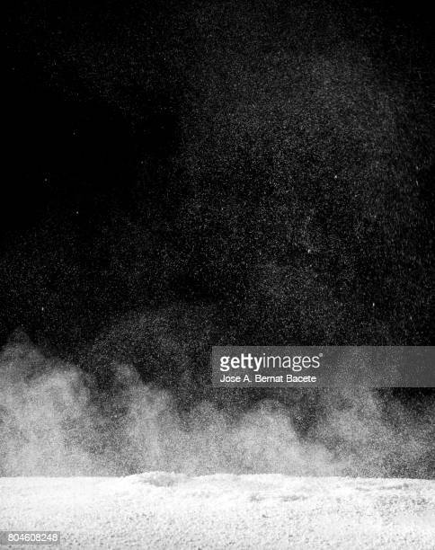Explosion of a cloud of powder of particles of colors white  and a black background