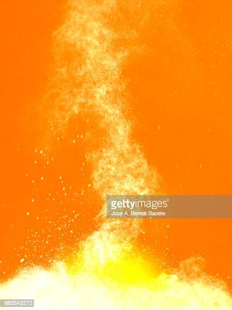 Explosion of a cloud of powder of particles of colors white and yellow and a orange background