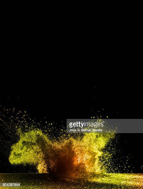Explosion of a cloud of powder of particles of colors yellow and orange and a black background