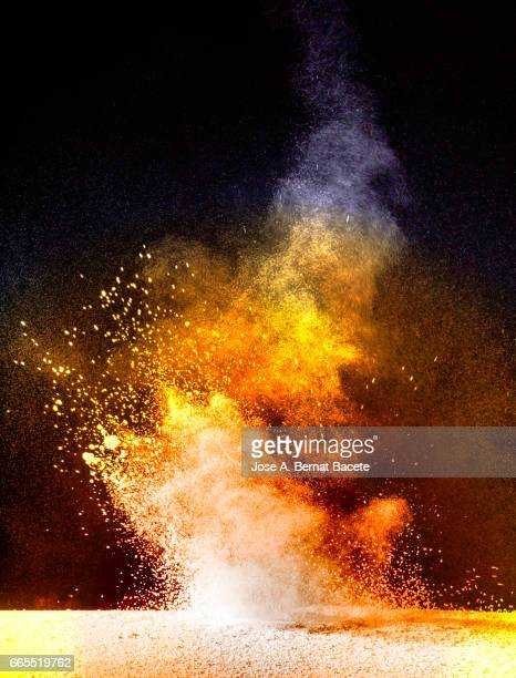 Explosion of a cloud of powder of particles of orange color on a black background