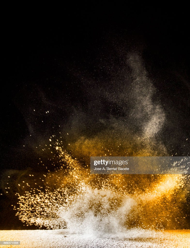 Explosion of a cloud of powder of particles of orange color on a black background : Stock Photo