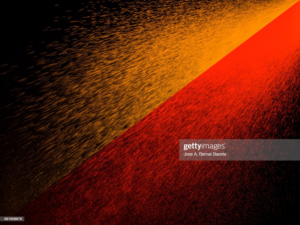 Explosion of water drops of colors red and orange, floating in the air on a black background : Stock Photo
