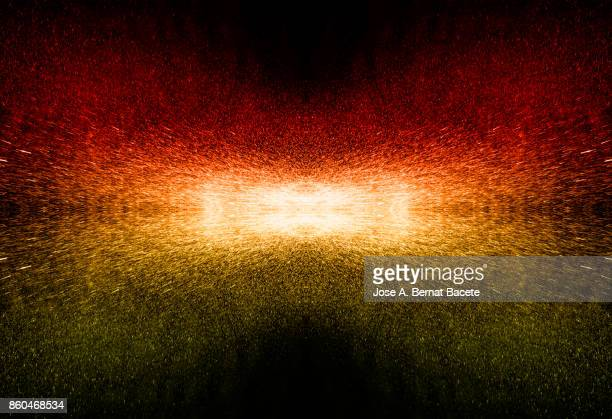 Explosion of water drops of colors red and yellow , floating in the air on a black background with textures