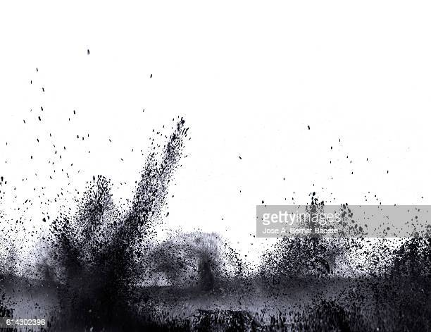 Explosion particles of black powder on a white background