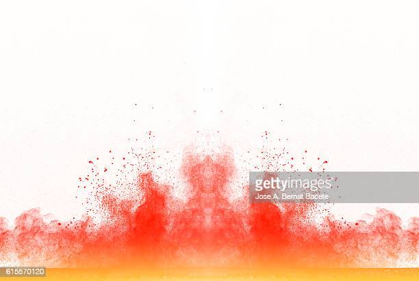 Explosion particles of orange and yellow  powder on a white background